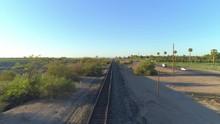 4K Aerial Of Desert Train Tracks At Sunrise Near Highway