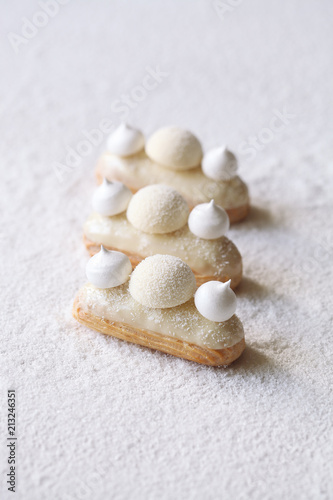Contemporary White Chocolate and Coconut Eclairs, on white background.