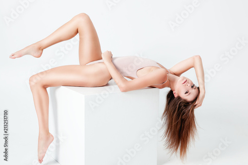 Obraz Fitness woman with a beautiful body posing over white background. Fitness, diet and beauty concept.  Pretty young woman sitting on cube. - fototapety do salonu