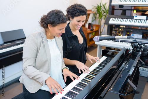 young women playing piano