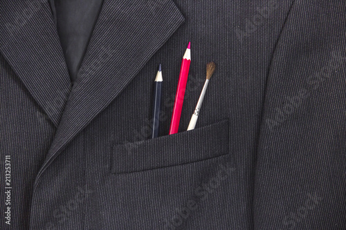 Fototapeta in the breast pocket of a dark black man's jacket a pencil and a brush lay in a light strip red blue obraz na płótnie
