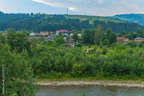 Foto op Plexiglas Groen blauw the flow of the river with stony shores near the resort town, located at the foot of the hill