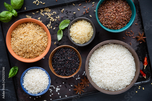 Variety of rice - red rice, black rice, basmati, whole grain rice, long grain parboiled rice and arborio rice - in bowls. Overhead view