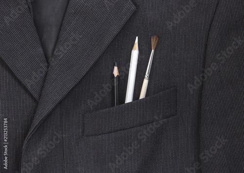 Fototapeta in the breast pocket of a dark black man's jacket a pencil and a brush lay in a light strip obraz na płótnie