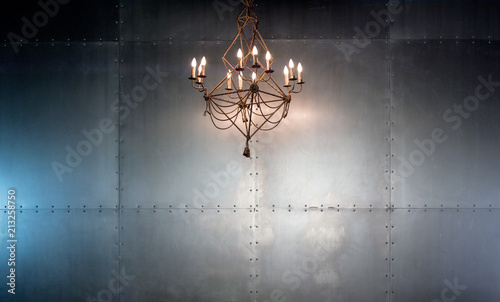 Illuminated chandelier against industrial metal wall