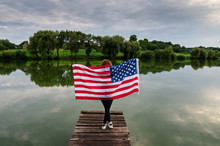 Girl On The River Bank With The US Flag.