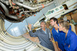 airplane engineer showing apprentices mechanics inside undercarriage