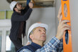 mature construction worker using level