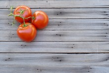 Three Vine Ripened Red Tomatoes On Wood Background