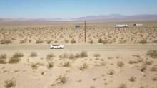 Side Aerial View Of A Car Driving On A Road In The Desert