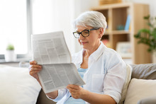 Age And People Concept - Happy Senior Woman Reading Newspaper At Home