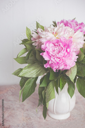 Fotografie, Obraz  Delicate pink and white peonies in a white beautiful vase on a marble table