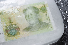 Close-up Of Frozen Chinese Currency On Table