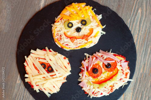 Raw Halloween pizza with monsters, above scene with decor on a black plate prepare for baked, idea for home party food, easy, healthy and delicious fun food party treats for kids