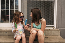 Smiling Sisters Holding Popsicles While Sitting On Steps