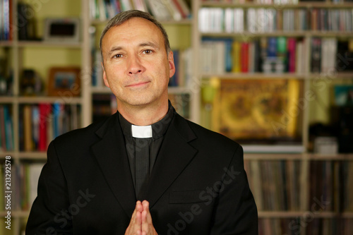 Fotografia A good looking catholic priest is praying into his library