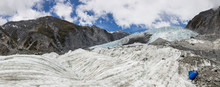 Panoramic View Of Franz Josef Glacier With Blue Drums Containing Emergency 'rescue' Supplies In The Foreground