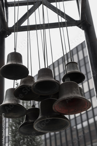 Old Bells Hanging from Ropes Outdoors with Modern Glass Building in Background, Poster