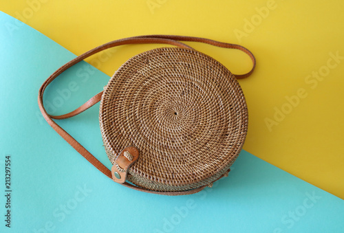 Photo Handwoven Boho Bali Round Rattan Beach Bag With Button Clip on a yellow and turq
