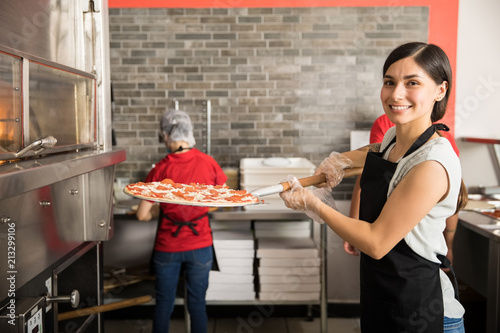 Wall Murals Pizzeria Pretty woman chef putting fresh made pizza in oven