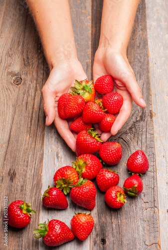 Fotografie, Obraz  Woman is holding fresh strawberries in hands on wood table