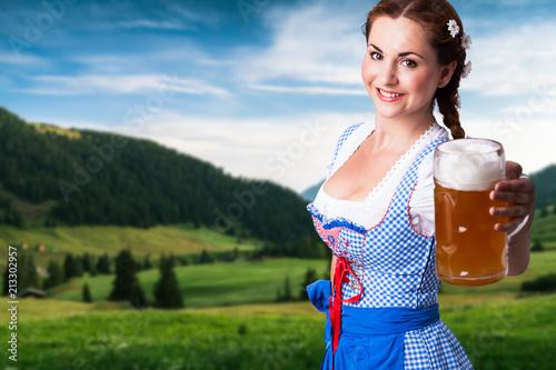 Plakát  junge Frau im Dirndl mit Bier vor Alpenlangschaft