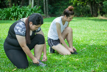 Asian Thin And Overweight Woman Tying Running Shoes Jogging In Park, Fat And Fitness Girls Running Exercise Workout Together .