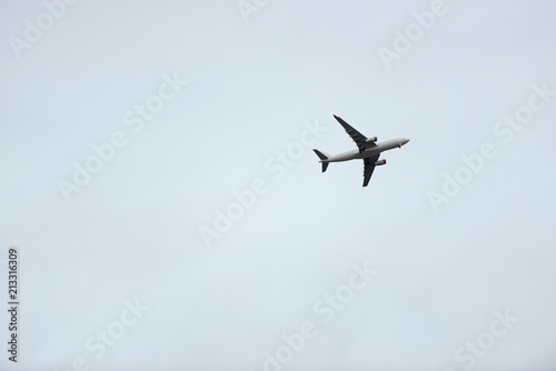 Airplane with gear down against a pale blue sky