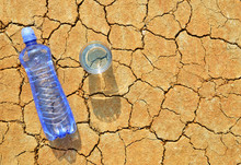 Bottle And Glass Of Water On Dry Cracked Soil. Concept Of Global Warming.
