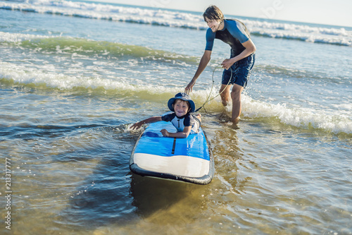 Foto op Aluminium Strand Father teaching his young son how to surf in the sea on vacation or holiday. Travel and sports with children concept