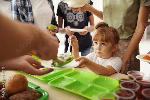 Photo Volunteers serving food for poor people indoors
