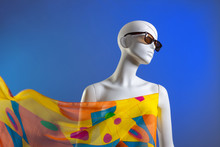 A Female Mannequin Wearing Sunglasses And A Bright Scarf-paced In The Wind Against A Blue Background. Summer Fashion.
