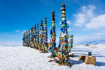 Wooden ritual pillars with colorful ribbons on cape Burkhan