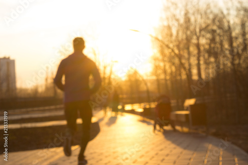 Fototapety, obrazy: Young man running in park during sunset