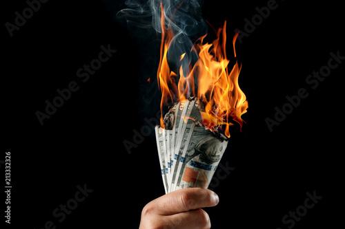 Valokuva  Male hand close-up, holds burning money in hands, burning US dollars
