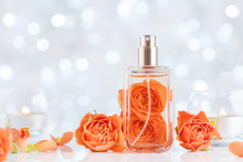 Perfume Bottle And Rose Flowers On White Table Against Bokeh. Beauty And Perfumery Background.