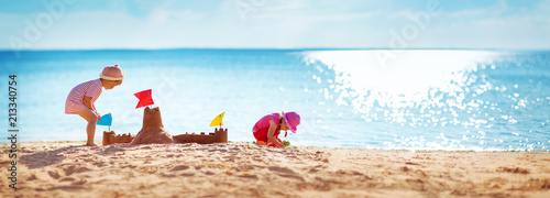 Fototapeta Boy and girl playing on the beach obraz
