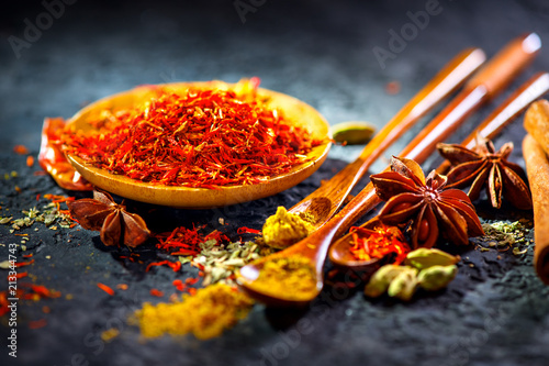 Canvas Prints Spices Saffron. Various Indian Spices on black stone table. Spice and herbs on slate background. Cooking ingredients
