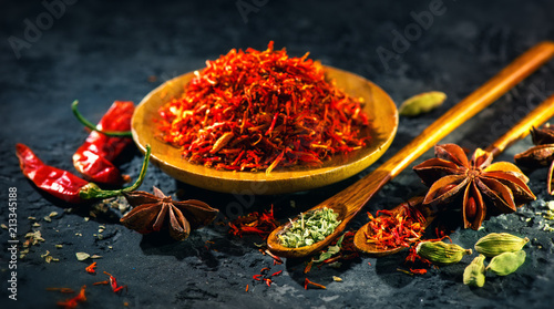 Deurstickers Aromatische Saffron. Various Indian Spices on black stone table. Spice and herbs on slate background. Cooking ingredients