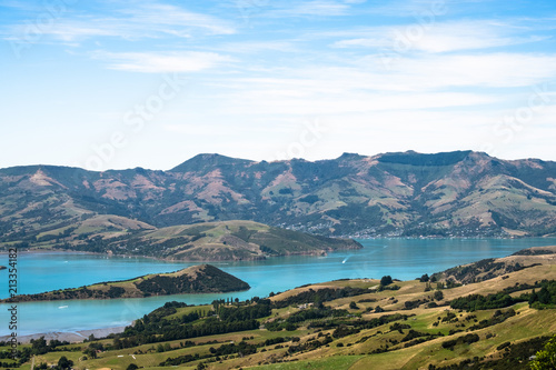 Deurstickers Wit Beautiful landscape of a peninsula. cloudy sky fresh ocean and grassland mountain. New Zealand agriculture.