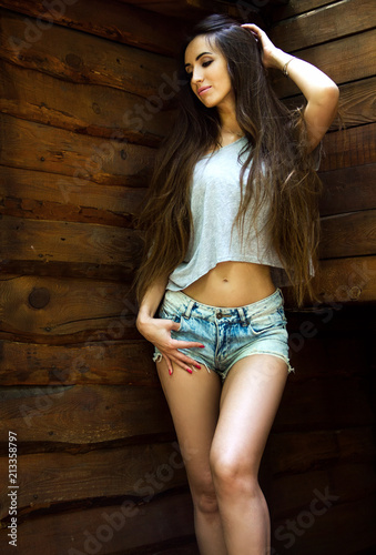 00ffe67f19 young brunette sexy girl in denim shorts and a vest with long hair is  standing with one hand in hair and smiling on wooden wall background