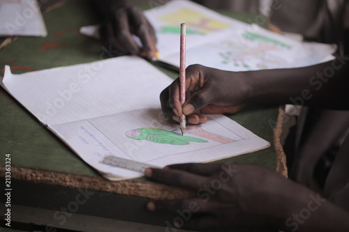 Spoed Foto op Canvas Afrika african education close up - macro photography of a black african school kid hand holding a pencil, inside a classroom in the Gambia, Africa