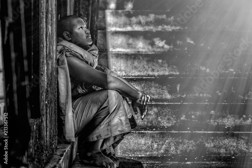 Fotografia  Black and white image of Thai Buddhist novice sitting at old temple door close t