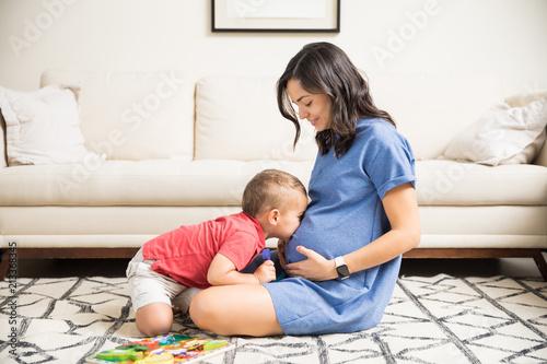 Photo Son Kissing Abdomen Of Pregnant Mom In Living Room