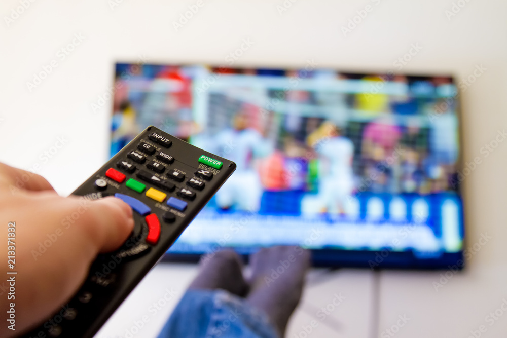 Fototapety, obrazy: Close-up macro of man's hand with TV remote control watching a soccer match