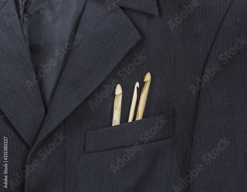 Fototapeta in a breast pocket of a dark black man's jacket in a light strip lay knitting wooden hooks of the different sizes obraz na płótnie