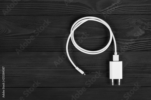 Foto Cable phone chargers on wood background