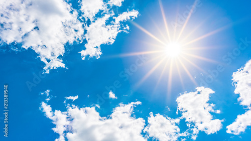 Foto  Sunny background, blue sky with white clouds and sun