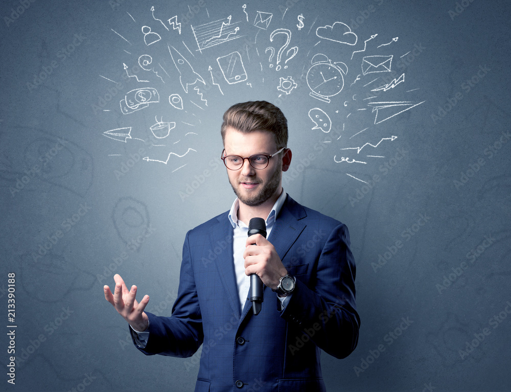Fototapeta Businessman speaking into microphone with mixed doodles over his head