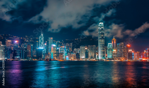 Fotomural  Futuristic City Skyline at Night with Colourful Lights and Reflections, Hong Kon